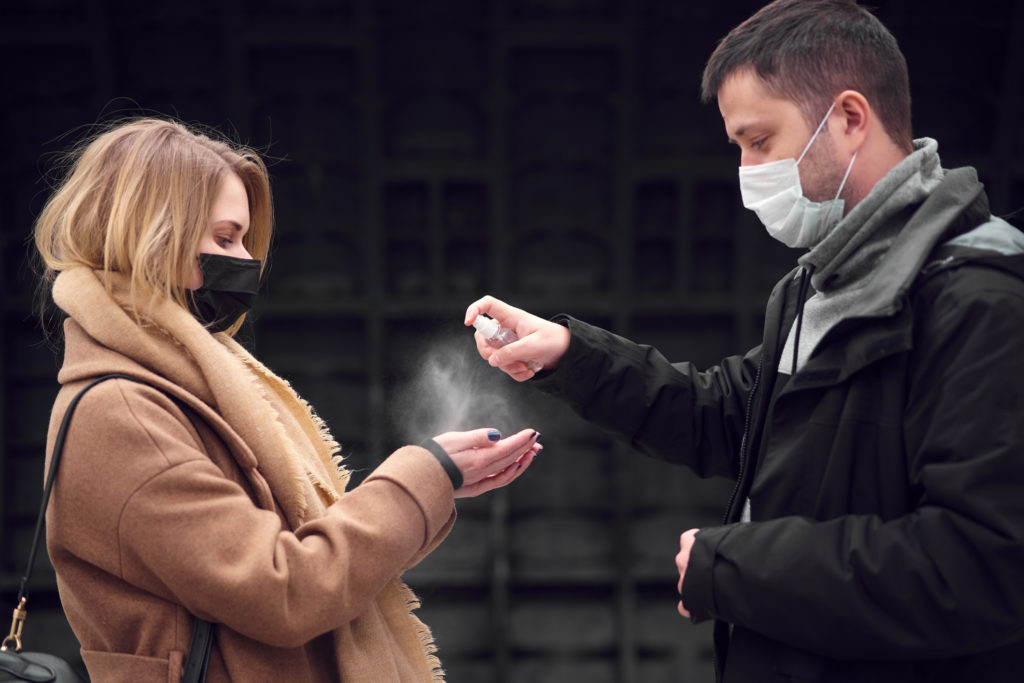 couple using spray sanitzer in public during the covid-19 pandemic