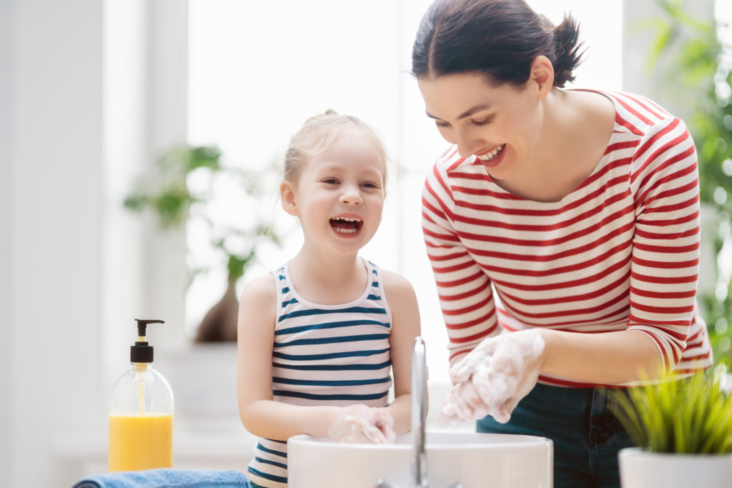 mother and daugther washing hands at home during hte covid-19 pandemic