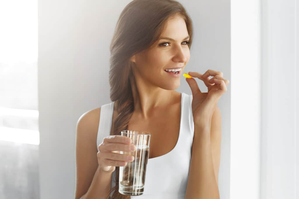 healthy woman taking supplements for her immune system