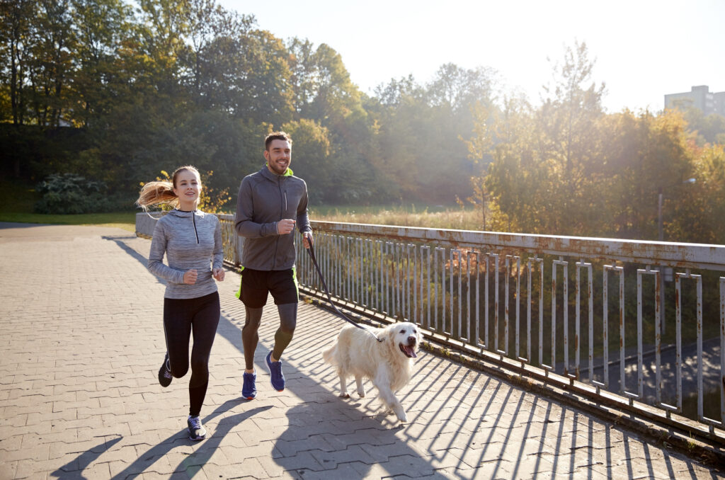 couple jogging with dog to boost energy levels